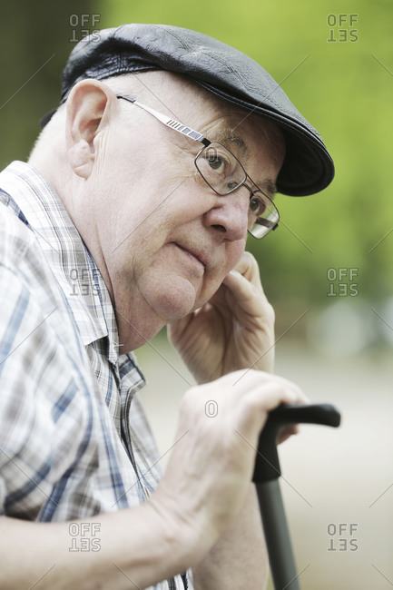 Germany- North Rhine Westphalia- Cologne- Senior man with cap and glasses in park- close up