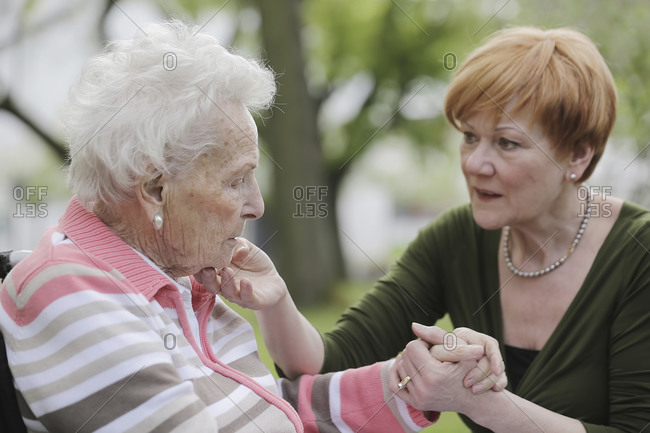 Germany- North Rhine Westphalia- Cologne- Senior woman holding hands of mature woman- close up