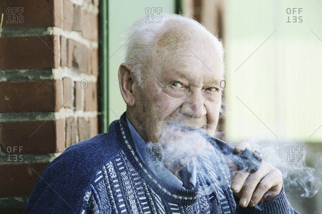 Germany- Portrait of senior man holding pipe- close up