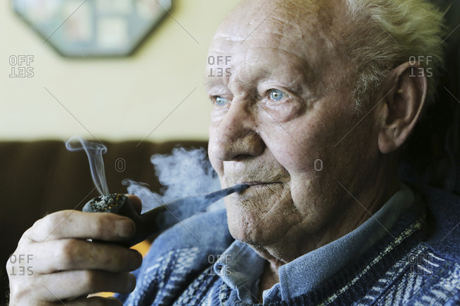 Germany- Senior man holding pipe and smoking