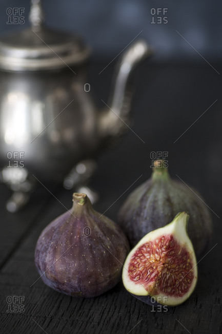Whole and sliced figs with silver teapot in the background