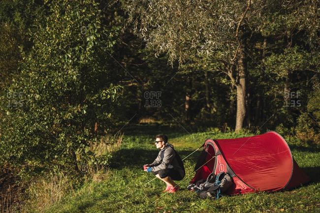 Man camping in Estonia- drinking coffee- watching sunrise