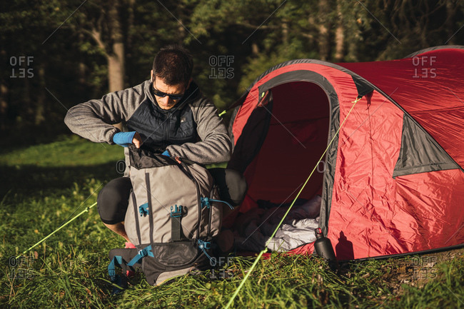 Man camping in Estonia- searching his backpack