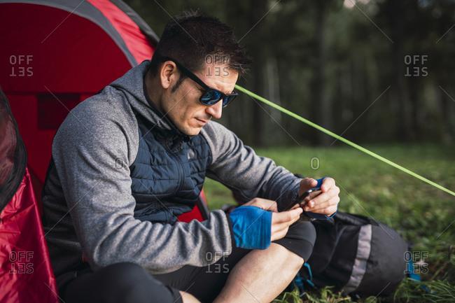 Man camping in Estonia- sitting in tent- using smartphone