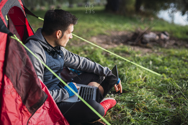Man camping in Estonia- sitting in tent- using laptop