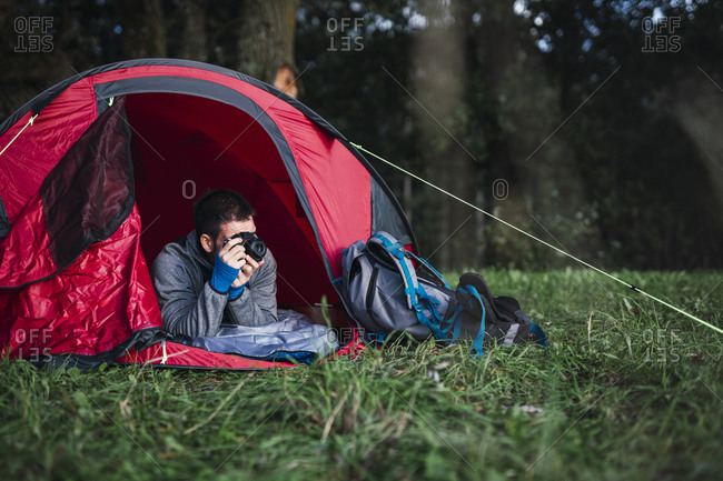 Man camping in Estonia- lying in his tent- taking pictures