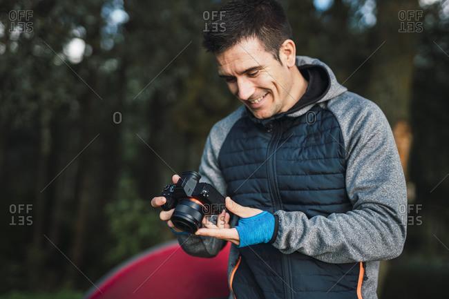 Man camping in Estonia- looking at his camera