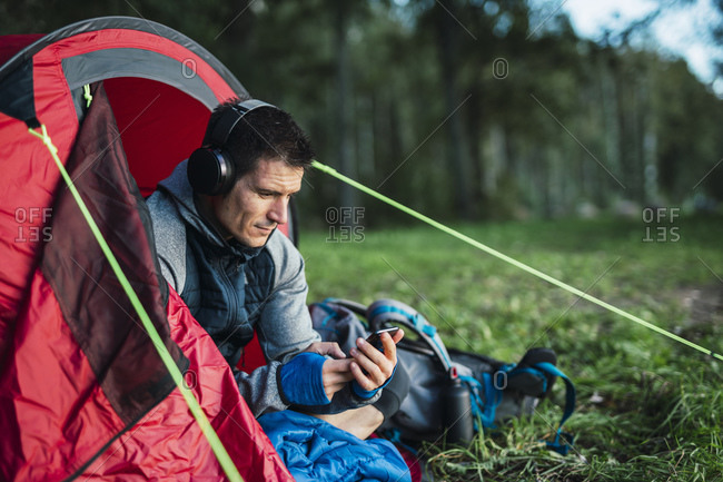 Man camping in Estonia- sitting in his tent- listening music from his smartphone