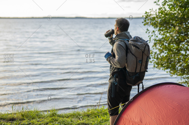 Man camping in Estonia- standing at lake with a backpack- drinking coffee