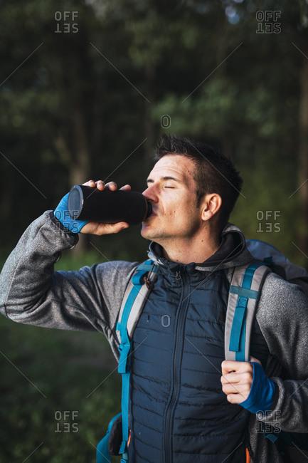 Man camping in Estonia- drinking water