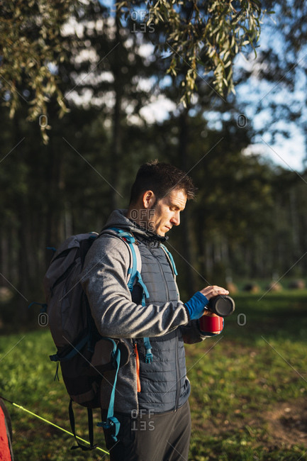 Man camping in Estonia- pouring water in a cup
