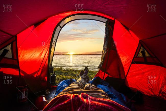 Man camping in Estonia- watching sunset lying in tent