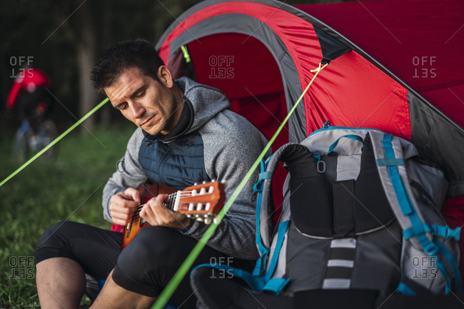 Man camping in Estonia- sitting in his tent- playing the ukulele