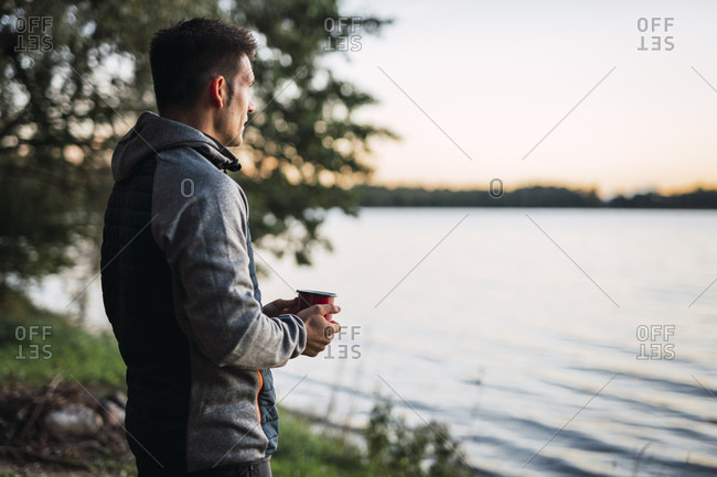 Man looking at the lake- drinking coffee