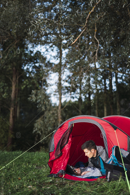 Man camping in Estonia- sitting in his tent- using smartphone