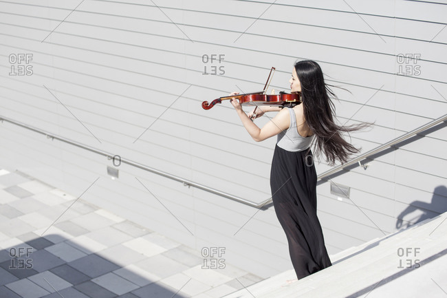 Young female Asian playing violin on stairs