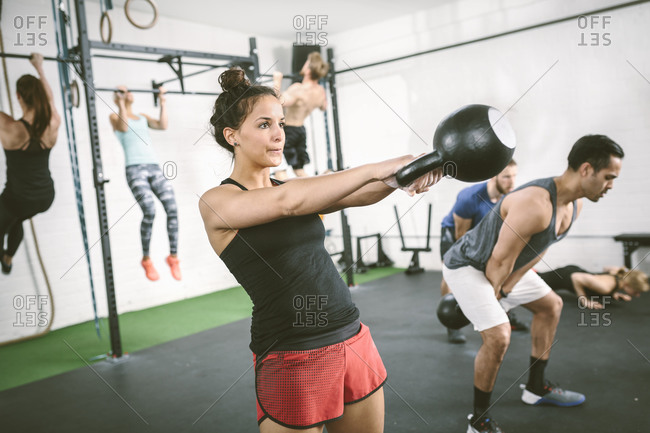 People in gym training with kettle bells