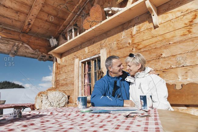 Germany- Bavaria- Winklmoosalm- Mature couple on terrace of alpine hut