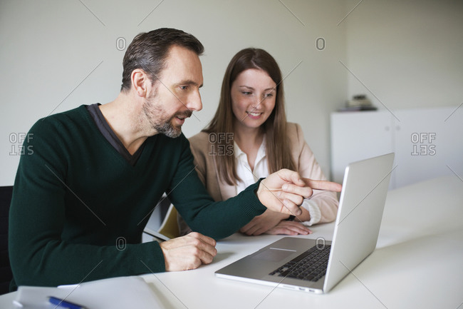 Businessman and employee using laptop at desk in office