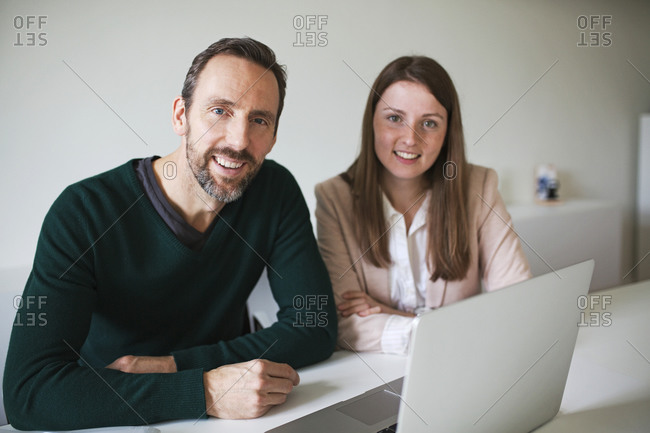 Portrait of smiling businessman and employee working at desk in office