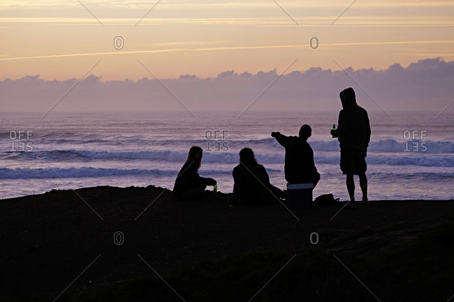 Portugal- Algarve- Sagres- Cordoama Beach- silhouette of four people at dusk