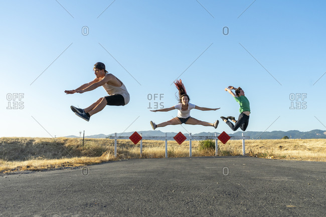 Three acrobats jumping mid-air on a dead-end street