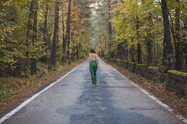 Rear view of shirtless young woman standing on country road