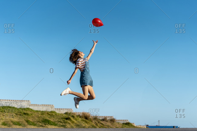 Jumping young woman- letting go of a red balloon