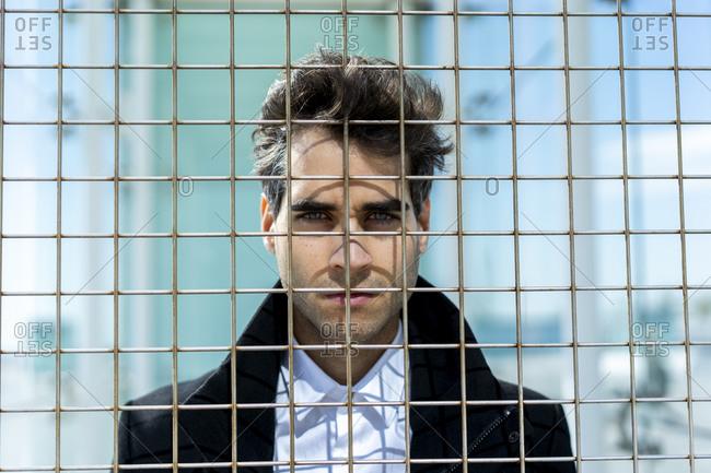 Portrait of serious businessman behind grid