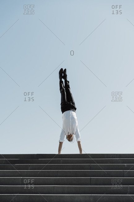 Businessman doing a handstand on top of stairs