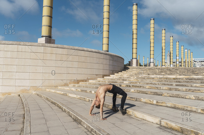Young man doing acrobatics on stairs outdoors