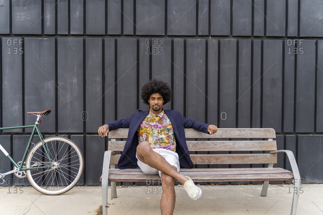 Stylish man with bicycle sitting on a bench