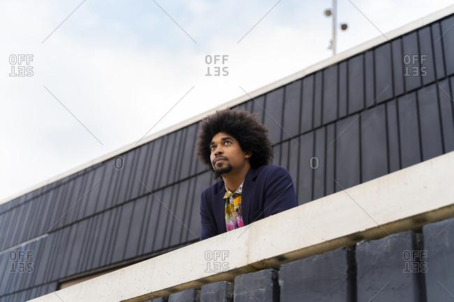 Portrait of stylish man behind a wall