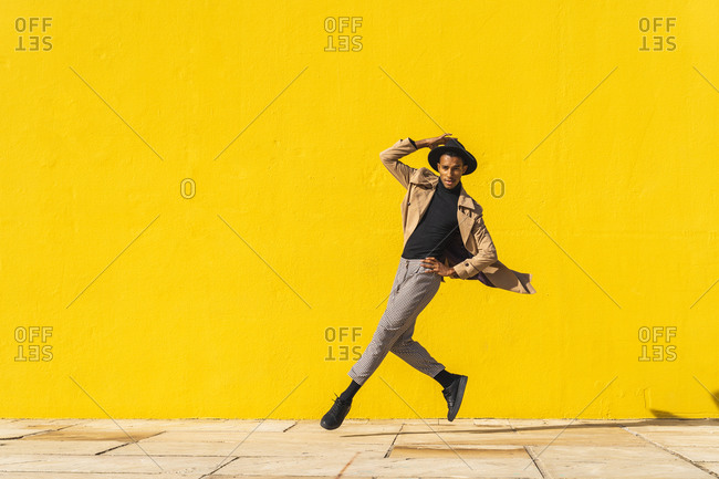 Young man dancing in front of yellow wall- jumping mid air