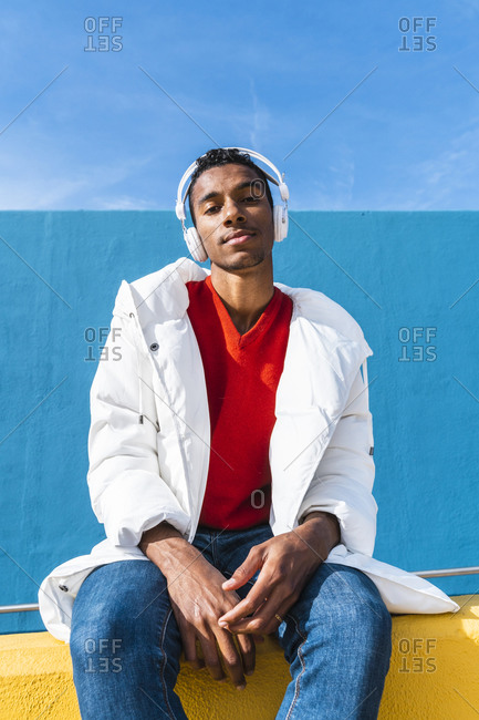Young trendy man sitting on yellow wall- listening music