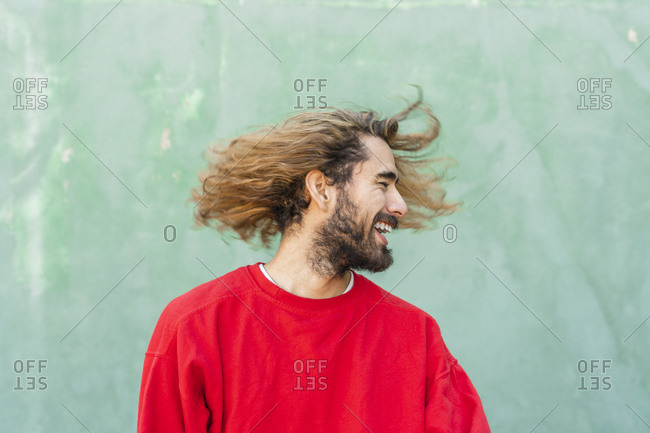 Bearded young man with tossing his hair in front of green wall