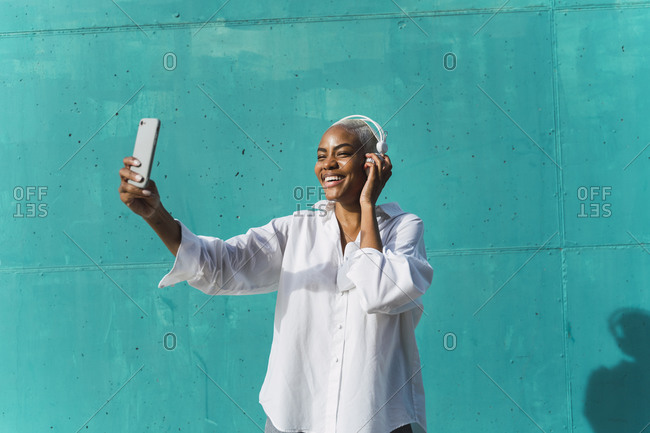 Beautiful woman standing in front of teal wall- listening music- taking selfies