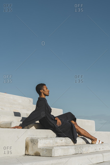 Young man wearing black kaftan sitting on concrete stairs under blue sky