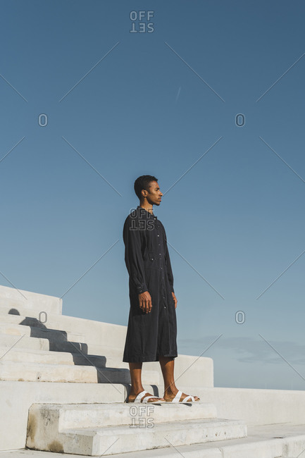Young man wearing black kaftan standing on concrete stairs under blue sky