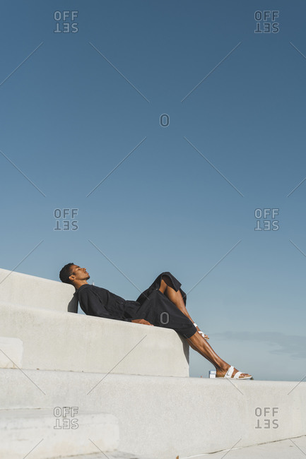 Young man wearing black kaftan lying on concrete stairs under blue sky