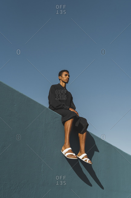 Young man wearing black kaftan sitting on blue wall