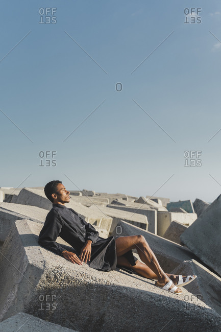 Young man wearing black kaftan lying on concrete blocks under blue sky