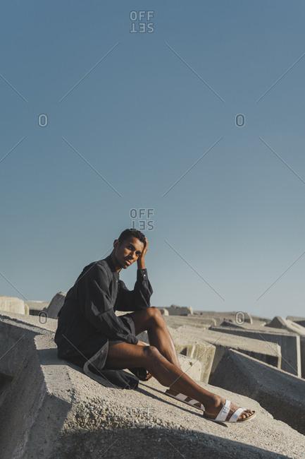 Young man wearing black kaftan sitting on concrete blocks under blue sky