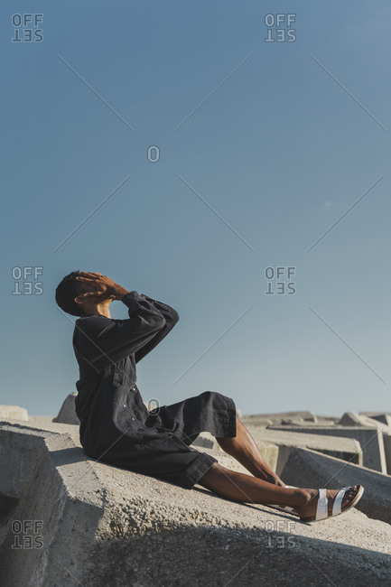 Young man wearing black kaftan sitting on concrete blocks under blue sky covering his face