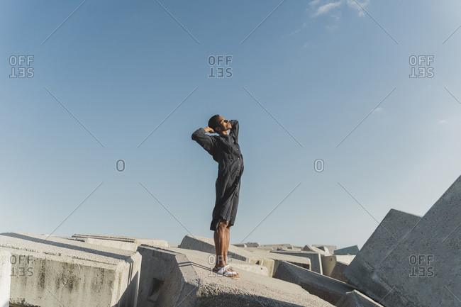Young man wearing black kaftan standing on concrete blocks under blue sky