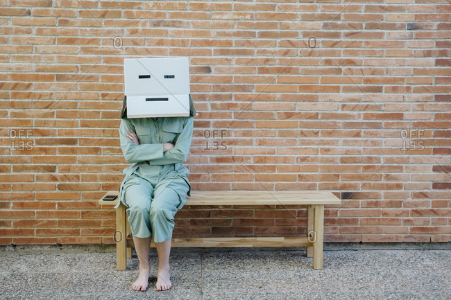 Woman sitting on bench in front of brick wall with serious  face on cardboard box- arms crossed