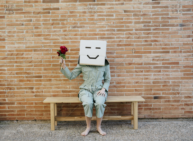 Woman holding red rose- wearing cardboard box with happy face- sitting on bench in front of brick wall