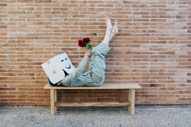 Woman holding red rose- wearing cardboard box with happy face- lying on bench in front of brick wall