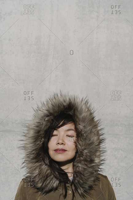 Portrait of woman in winter coat in the background of a wall