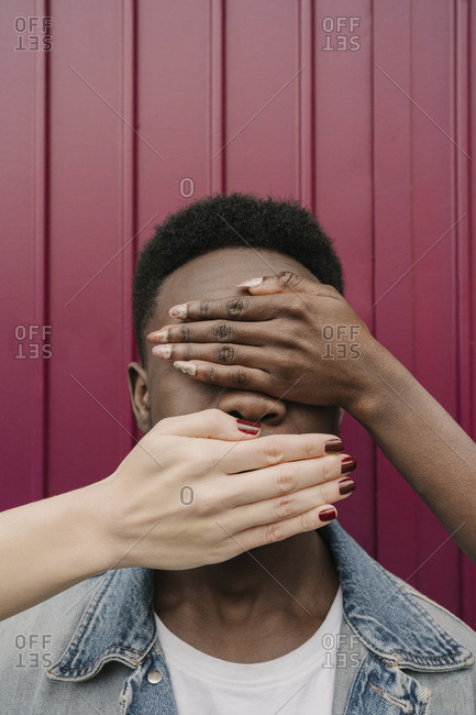 Female hands covering man's eyes and mouth